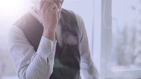 Mens die op telefoon met gelukkige glimlach op gezicht, succesvolle startbedrijfwerkgever spreken stock video