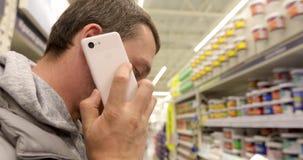 Mens die op telefoon in opslag spreken stock footage