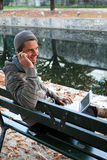 Mens die op Telefoon spreekt en op Netbook typt Royalty-vrije Stock Foto