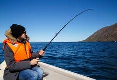 Mens die op water vissen Stock Foto