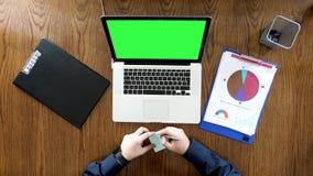 Mens die op zijn kantoor aan een bureau werken waar computer met het groene scherm is stock footage