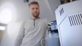 Mens die op zijn koffie wachten in de ochtend vroeg thuis te maken stock video