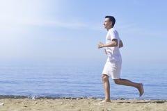 Mens die op zonnig strand lopen Onherkenbare lichaamsjogging op oceaanstrand Het lopen op tropisch strand Aantrekkelijke mens die stock afbeelding