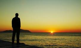Mens die op zonsondergang kijkt Stock Foto