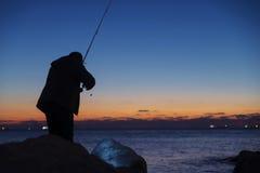 Mens die op zonsondergang vissen Stock Afbeelding