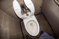 Mens die in openbaar toilet urineren stock afbeeldingen