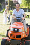 Mens die in openlucht grasmaaier drijft die met familie glimlacht Royalty-vrije Stock Afbeelding