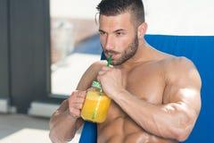 Mens die Oranje Juice Resting On Sun Loungers drinken royalty-vrije stock foto