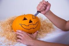 Mens die oranje pompoen hefboom-o-Lantaarn voor Halloween-partij snijden Stock Foto