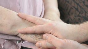 Mens die oude gerimpelde handen van bejaarde houden stock videobeelden