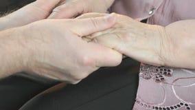 Mens die oude gerimpelde handen van bejaarde houden stock video