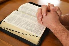 Mens die over een Bijbel bidden Royalty-vrije Stock Afbeeldingen