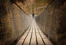 Mens die over een kabelbrug lopen Stock Foto