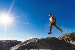 Mens die over hiaat op bergstijging springen royalty-vrije stock afbeelding