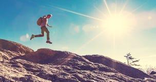 Mens die over hiaat op bergstijging springen stock afbeelding