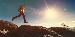 Mens die over hiaat op bergstijging springen stock foto's
