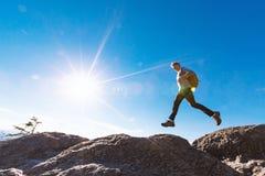 Mens die over hiaat op bergstijging springen stock afbeeldingen