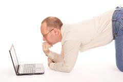 Mens die over Internet thuis werken Stock Foto's