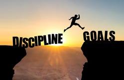 Mens die over kloof met tekst DISCIPLINE/GOALS springen stock illustratie