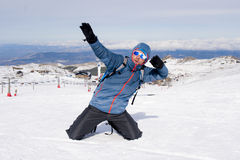 Mens die overwinningsteken na de piekvoltooiing van de toptrekking in sneeuwberg doen op de winterlandschap Royalty-vrije Stock Foto's