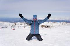 Mens die overwinningsteken na de piekvoltooiing van de toptrekking in sneeuwberg doen op de winterlandschap Stock Afbeelding