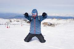 Mens die overwinningsteken na de piekvoltooiing van de toptrekking in sneeuwberg doen op de winterlandschap Royalty-vrije Stock Fotografie