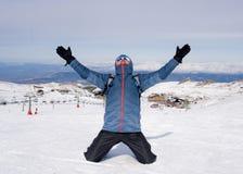 Mens die overwinningsteken na de piekvoltooiing van de toptrekking in sneeuwberg doen op de winterlandschap Royalty-vrije Stock Afbeeldingen