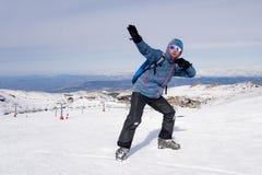 Mens die overwinningsteken na de piekvoltooiing van de toptrekking in sneeuwberg doen op de winterlandschap Royalty-vrije Stock Foto