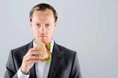 Mens die in pak heerlijk de eten haalt vleesbroodje weg royalty-vrije stock afbeeldingen