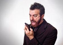 Mens die in pak in zijn mobiele telefoon schreeuwen Stock Afbeeldingen
