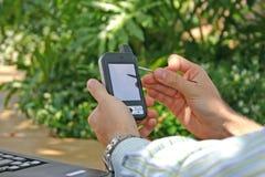 Mens die PDA/Smartphone buiten gebruikt Stock Foto