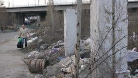 Mens die plastiek zoeken bij huisvuilstortplaats in stad stock video