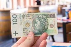 Mens die Poolse zloty rekening 100 in openluchtrestaurantterras houden Stock Fotografie