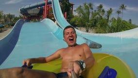 Mens die pret hebben, die bij waterpark glijden stock videobeelden