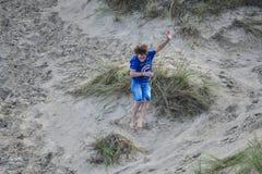 Mens die pret op zandstrand hebben met van het grasgebied en zand duinen tijdens vakanties stock fotografie