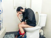 Mens die problemen in toilet hebben royalty-vrije stock afbeelding