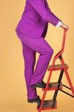 Mens die in Purper kostuum ladder beklimmen royalty-vrije stock afbeeldingen