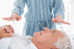 Mens die Reiki-behandeling door therapeut ontvangen Stock Afbeeldingen