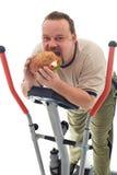 Mens die reusachtige hamburger op een trainerapparaat eet Royalty-vrije Stock Fotografie
