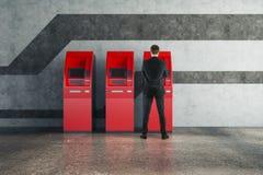 Mens die rode ATM-machine met behulp van Stock Fotografie