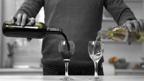 Mens die rode en witte wijn gieten in twee glazen stock video