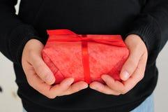 Mens die rode gift houdt Royalty-vrije Stock Afbeeldingen