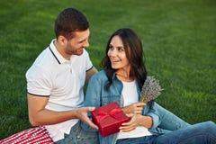 Mens die rode giftdoos geven aan zijn meisje stock fotografie