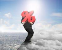 Mens die rood percentageteken op rand met cloudscape dragen citysc Stock Fotografie