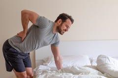 Mens die rugpijn na het slapen in bed voelen royalty-vrije stock fotografie