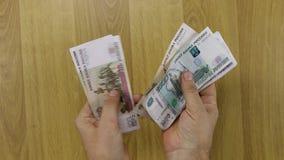 Mens die Russisch papiergeld, roebels tellen stock video
