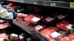 Mens die ruw rundvlees in kruidenierswinkelopslag selecteren stock videobeelden