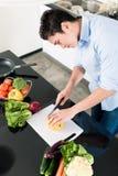 Mens die salade voorbereiden en in keuken koken Stock Afbeelding
