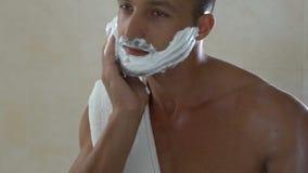 Mens die scheercrème op gezicht toepassen, die veiligheidsscheermes in badkamers in ochtend houden stock video