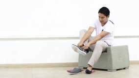 Mens die schoenen het zitten dragen stock footage